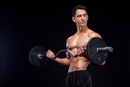 Athlete bodybuilder. Brutal strong muscular athletic man pumping up muscles with barbell on black background. Workout bodybuilding concept. Imagens
