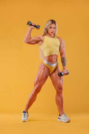 Athlete bodybuilder. Strong athletic woman on steroids with dumbbells on yellow background wearing in sportswear. Fitness and sport motivation.