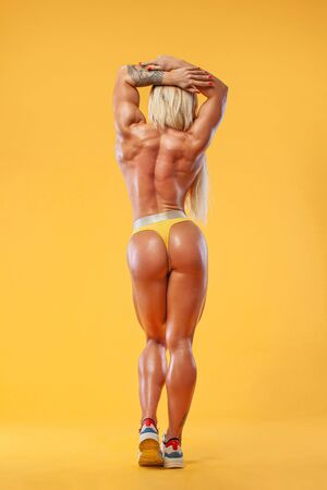 Athlete bodybuilder. Strong athletic woman on steroids on yellow background wearing in sportswear. Fitness and sport motivation. Imagens