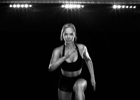 Sprinter and fit athlete runner running on the black background. The concept of a healthy lifestyle and sport. Woman in black and white sportswear.