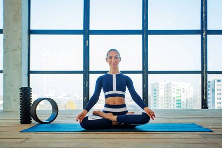 Portrait of a beautiful young woman sitting in yoga pose