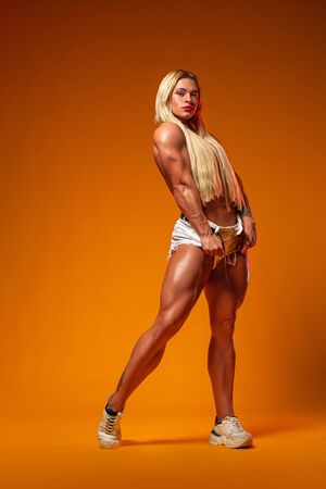 Athlete bodybuilder. Strong athletic woman on steroids on yellow background. Fitness and sport motivation. Imagens