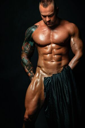 Muscular young sexy cute man bodybuilder isolated on black background.