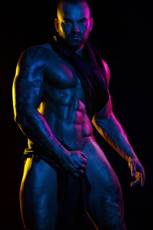 Muskulöser junger gutaussehender Mann Bodybuilder auf schwarzem Hintergrund isoliert. Farbfilter.