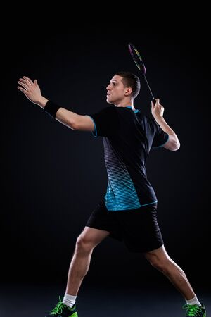 Badminton player in sportswear with racket and shuttlecock on black background.