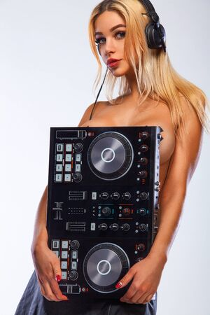 Poster for DJ party or album cover. Portrait of sexy woman with deck playing music on white background Reklamní fotografie