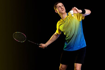 Badminton player in sportswear with racket and shuttlecock on black background. Individual sports. Sports recreation.
