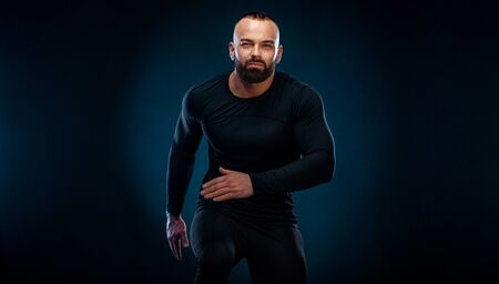 Muscular young fitness sports man athlete in compression garment. Workout in gym
