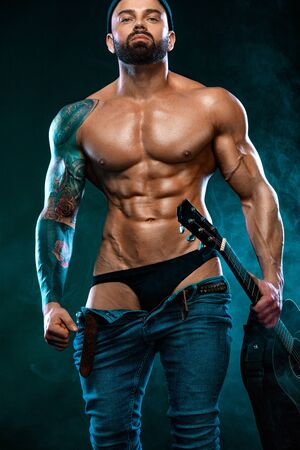 Strong and fit man bodybuilder with guitrar shows abdominal muscles. Sporty muscular guy athlete. Sport and fitness concept. Mens fashion.