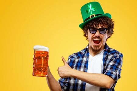 Saint Patrick Day. Young Oktoberfest man serving big beer mug with drink isolated on yellow background. Guy showing thumbs up sign with fingers. Stok Fotoğraf