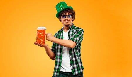 St Patrick Day. Young Oktoberfest man serving big beer mug with drink isolated on yellow background. Guy showing ok sign with fingers.