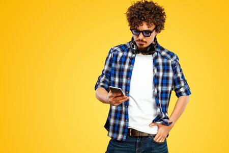 European man with curly hair in blue sunglasses with mobile phone or smarphone. Handsome smiled stylish hipster in plaid shirt posing over yellow background. Stock fotó