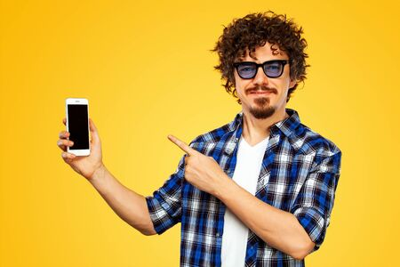 European man with curly hair in blue sunglasses with mobile phone or smarphone. Guy pointing to looking on the screen. Handsome stylish hipster in plaid shirt posing over yellow background.
