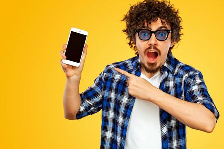 European man with curly hair in blue sunglasses pointing to looking on the screen of mobile device or smarphone. Handsome stylish hipster in plaid shirt posing over yellow background. Stock fotó