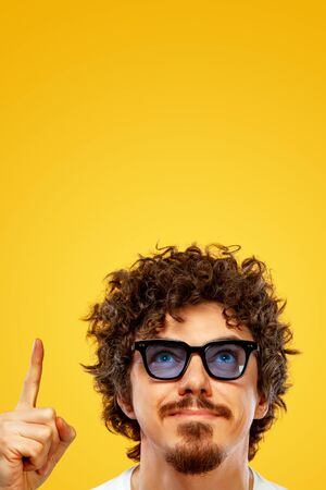 Portrait of happy bearded man with curly hair pointing finger up at copyspace isolated over yellow background. Guy in blue sunglasses pick on great idea.
