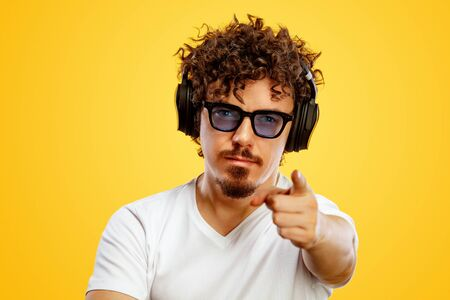 Portrait of happy bearded man with curly hair pointing finger at screen isolated over yellow background. Guy in blue sunglasses and headphones pick on great idea. Stock fotó