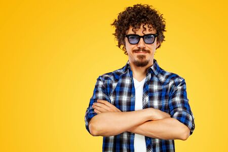 European man with curly hair in blue sunglasses. Handsome smiled stylish hipster in plaid shirt posing over yellow background with crossed hands.