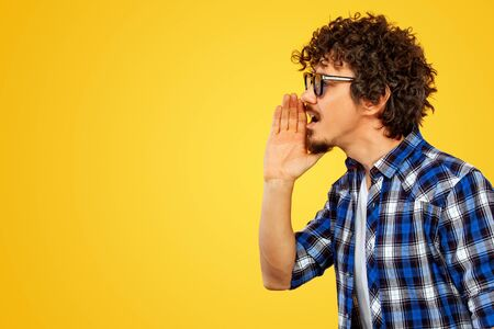 Closeup portrait of handsome happy european man with beard and curly hair in blue shirt opened mouth widely and shouting loud. Hispter isolated on yellow background. Positive emotions.