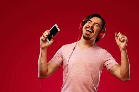 Handsome happy european man with beard in red t-shirt smiling and dancing isolated on red background. Guy in headphones listening to music on smartphone. Lifestyle concept.