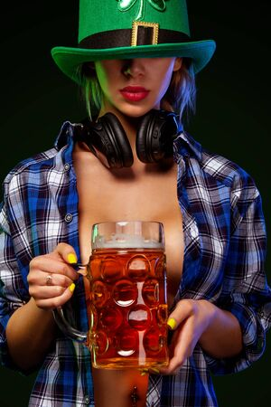 Saint Patrick Day. Young sexy Oktoberfest girl waitress in green har serving big beer mugs with beer isolated on dark background. St Patricks day celebration.
