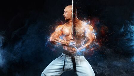 Karate fighter on black background with smoke. Shirtless man samurai with Japanese sword. Fit man sportsmen bodybuilder physique and athlete. Mens sport motivation.