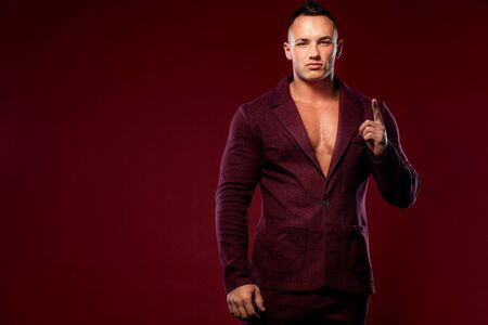 Portrait of handsome stylish man bodybuilder with torso in elegant suit. Guy showing thumbs up sign with fingers.