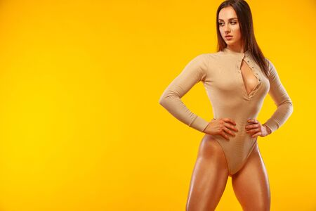 Sporty fit woman, athlete make fitness exercises on yellow background.