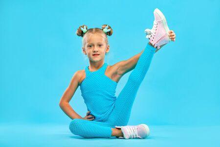 Kid girl doing fitness exercises on pink and pink background in sportswear. Sports concept.