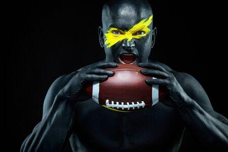 Fan de football américain avec ballon sur fond noir. Remise en forme et motivation sportive. Ajustement fort et gars athlétique en peinture corporelle comme un super héros. Banque d'images