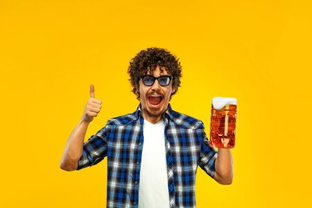 St Patrick Day. Young Oktoberfest man serving big beer mug with drink isolated on yellow background. Guy showing thumbs up sign with fingers. Zdjęcie Seryjne