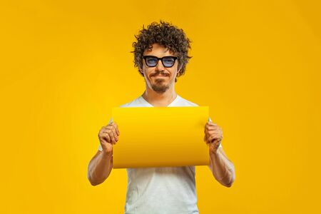 Mab with blank banner or poster. Handsome happy european guy with beard in white t-shirt smiling isolated on yellow background. Lifestyle concept. Zdjęcie Seryjne