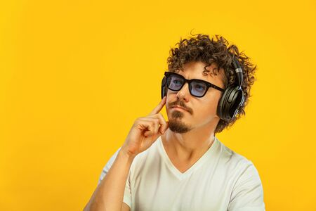 Portrait of happy bearded man with curly hair pointing finger at screen isolated over yellow background. Guy in blue sunglasses and headphones pick on great idea. Zdjęcie Seryjne