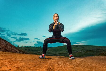 Workout with bands or expander outdoors. Individual sports recreation. Sporty and fit young woman athlete have a training on the sky background. Concept of a healthy lifestyle and sport.