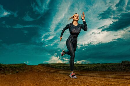 Workout outdoor. Sporty young woman and fit athlete runner running on the sky background. The concept of a healthy lifestyle and sport. Woman in black outfit. Zdjęcie Seryjne