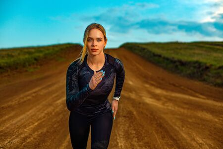 Fitness outdoors. Sporty young woman and fit athlete runner running on the sky background. The concept of a healthy lifestyle and sport. Woman in black outfit. Zdjęcie Seryjne
