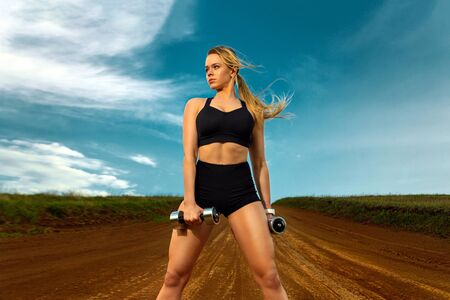 Sporty and fit woman athlete doing training with dumbbells on the sky background. The concept of a healthy lifestyle and sport. Individual sports recreation. Zdjęcie Seryjne