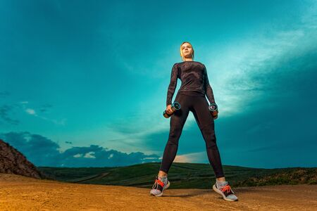 Workout outdoor. Sporty and fit woman athlete doing training with dumbbells on the sky background. The concept of a healthy lifestyle and sport. Individual sports recreation.