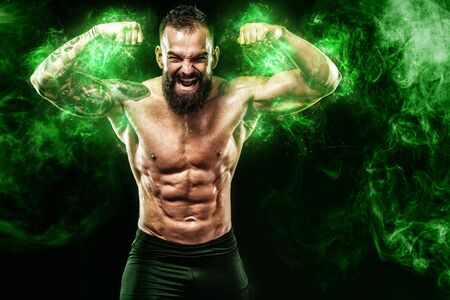 Athlete in green energy lights. Sportsman muay thai boxer celebrating victory on black background with smoke. Copy Space. Sport concept. Archivio Fotografico
