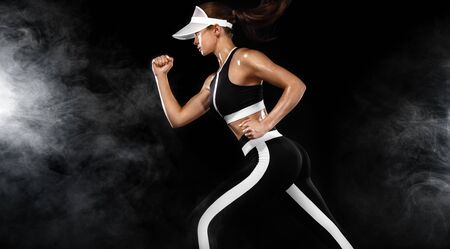 Fit woman athlete runner on black background. Strong athletic girl sprinter, running wearing in sports outfit. Fitness and sport motivation. Run concept with copy space.