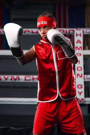 Kids sport concept. Girl sportsman muay thai boxer fighting in gloves in boxing gym.