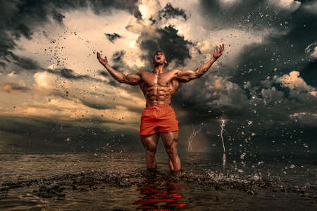 Fit athlete bodybuilder on the beach. Attractive young man lifeguard on a tropical seashore. A thunderstorm is behind the man.