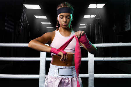 Kids sport concept. Girl sportsman muay thai boxer fighting in gloves in boxing gym.
