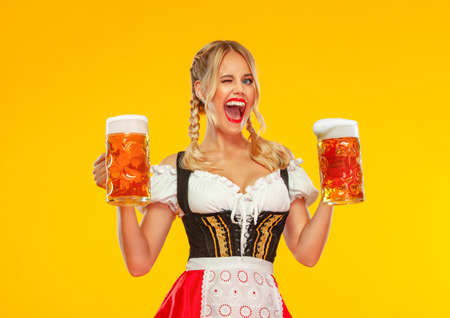 Young Oktoberfest girl waitress, wearing a traditional Bavarian or german dirndl, serving big beer mugs with drink isolated on yellow background. Woman pointing to looking left.