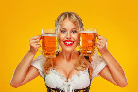 Young Oktoberfest girl waitress, wearing a traditional Bavarian or german dirndl, serving big beer mugs with drink isolated on yellow background. Woman pointing to looking up.