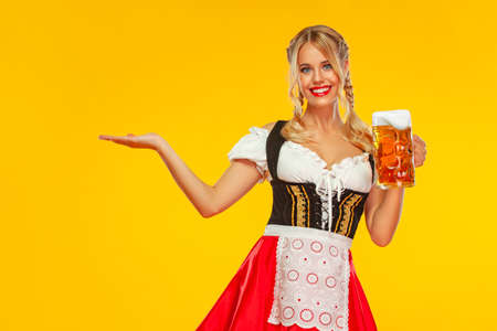 Young Oktoberfest girl waitress, wearing a traditional Bavarian or german dirndl, serving big beer mug with drink isolated on yellow background. Woman pointing to looking left.