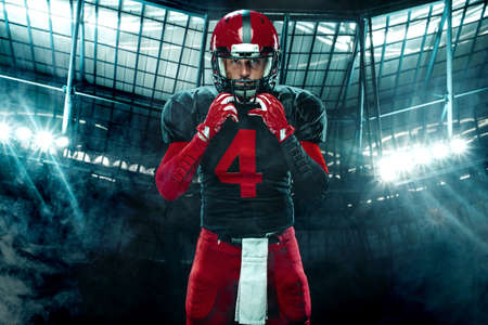 American football player, athlete sportsman in red helmet on dark background with smoke. Sport and motivation wallpaper. 版權商用圖片