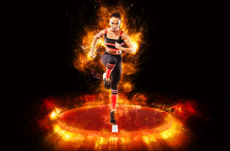 Runner concept. A strong athletic, women sprinter, running wearing in the sportswear, fitness and sport motivation. Power and fire energy of run. Foto de archivo