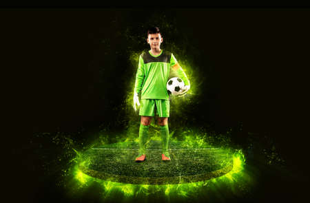 Soccer player. Boy goalkeeper in green sportswear with ball. Sport concept. Football player. Zdjęcie Seryjne
