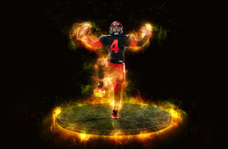 American football player, athlete sportsman in red helmet on dark background with fire. Sport and motivation wallpaper. Man celebrates victory