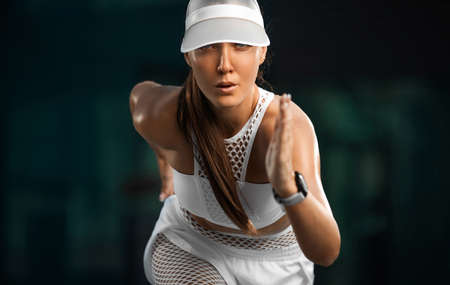 Strong athletic woman sprinter running in the city wearing white sportswear. Fitness and sport motivation outdoor in morning. Runner concept with copy space.